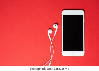 Smartphone with Blank Screen Connects to Earphones with Spiral Cable on Red Background Top View.