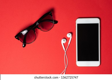 Smartphone with Blank Screen Connects to Earphones with Spiral Cable on Red Background Top View,Sunglasses.