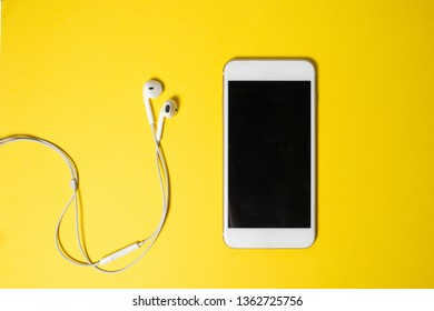 Smartphone with Blank Screen Connects to Earphones with Spiral Cable on yellow Background Top View