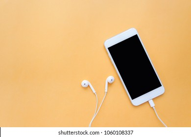 Smartphone with Blank Screen Connects to White Earphones on Orange Background Top View