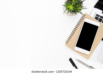 Smartphone with blank screen is on top of laptop computer over white office desk table. Top view with copy space, flat lay.