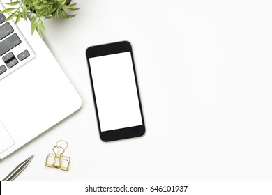 Smartphone with blank screen is on top of white table. Top view with copy space, flat lay.