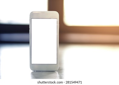 smartphone with blank screen standing on wooden table.