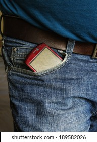 Smartphone with blank screen sticking out of the back pocket in a  jeans, clipping path for the screen to add your own text.