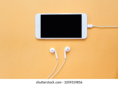 Smartphone with Blank Screen and White Earphones on Orange Background Top View