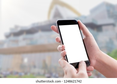 Smartphone blank screen in woman hands over blurred background at shopping mall.