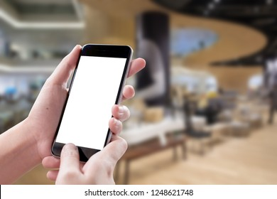 Smartphone blank screen in woman hands over blurred background at Holel.