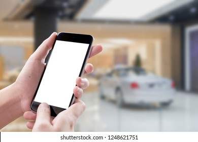 Smartphone blank screen in woman hands over blurred background at Showroom.
