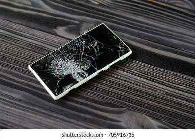 Smartphone with broken screen on dark wooden background