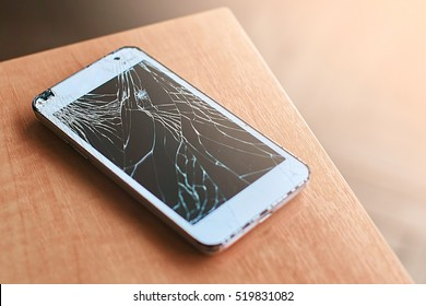 Smartphone with broken screen on the wooden table