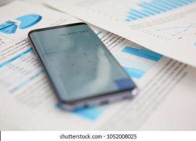 Smartphone calculator and financial statistics ondisplay tablet at office table closeup. Internal Revenue Service inspector sum check irs investigation earnings savings loan and credit concept