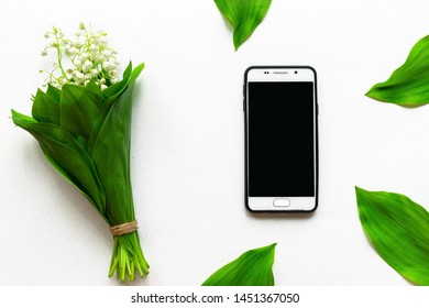 Smartphone in a case and flovers on white background. Flat lay with flovers and phone. Top view mockup