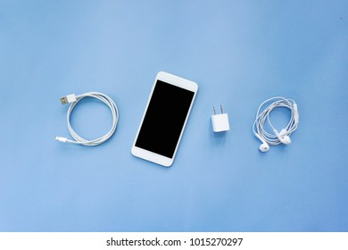 Smartphone, Charger, Spiral USB Cable, and Earphones on Blue Background Top View