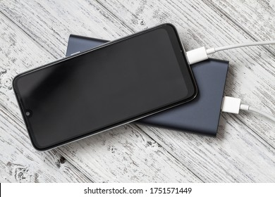 The smartphone is charging from external powerbank with cable on a gray wooden background. Closeup, selective focus