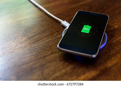 Smartphone charging on a charging pad. Wireless charging