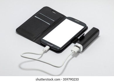 Smartphone is charging from the power bank isolated on white