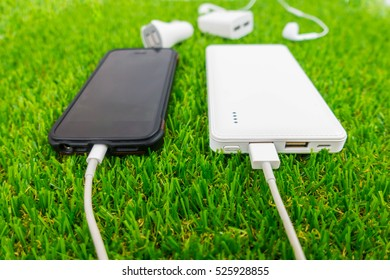 Smartphone charging with power bank on grasses