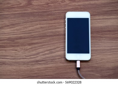 Smartphone charging with power bank on wood background