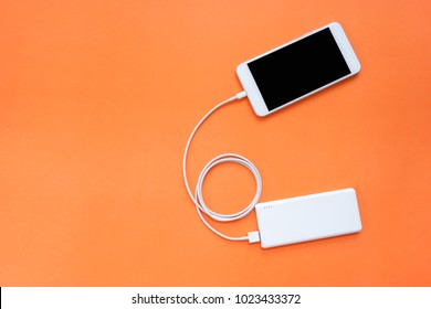 Smartphone Charging Through Power Bank with Spiral USB Cable on Orange Background Top View