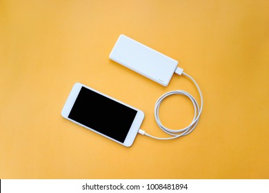 Smartphone Charging Via Power Bank with Spiral USB Cable on Orange Background Top View
