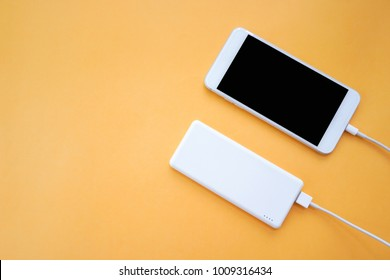 Smartphone Charging with White Power Bank on Orange Background Top View