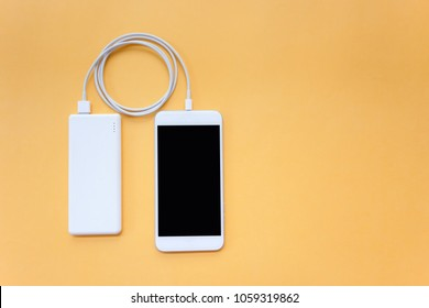 Smartphone Charging with White Power Bank Through Spiral USB Cable on Orange Background Top View