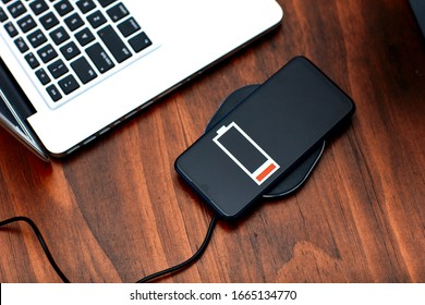 The smartphone charging wirelessly is on the desk,Charge sharing concept