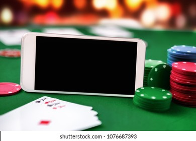 Smartphone with chip cards and four aces. Online poker gaming and gambling.