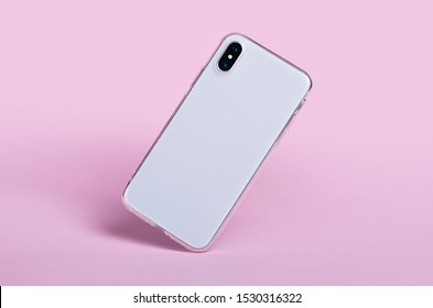 Smartphone in clear phone silicone case falls down, back view. iPhone X case mockup isolated on pink background