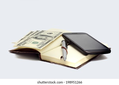 smartphone, closed notebook with gray metal ballpoint pen and nested denominations hundred dollars