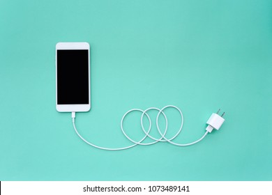 Smartphone Connects to Charger through USB Cable on Turquoise Background Top View
