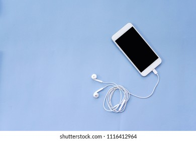 Smartphone Connects to Earphones on Blue Background Top View with Copy Space