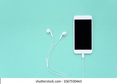 Smartphone Connects to Earphones on Turquoise Background Top View