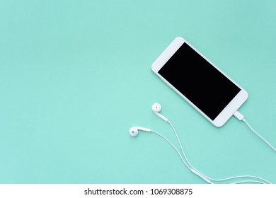 Smartphone Connects with White Earphones on Turquoise Background Top View