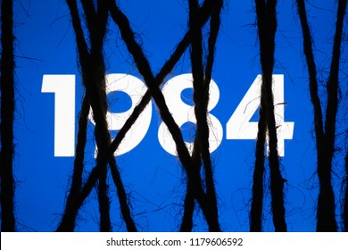 "Smartphone in the dark, tightly wrapped and tied with coarse jute rope bondage with glowing blue screen with white text ""1984"". Concept of censorship on social networks. Totalitarianism. Dictatorship"