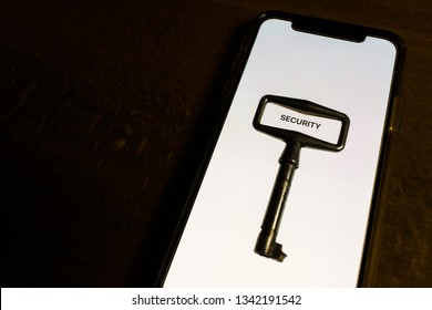 smartphone data protection concept - close-up of key lies on the white screen of the smartphone as a symbol of personal data security