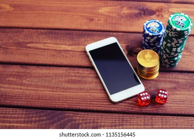 Smartphone, dice, poker chips and ethereum coins. Online casino with payment by cryptocurrency concept.
