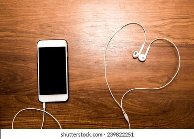 Smartphone with earphone on wood table.