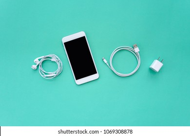 Smartphone, Earphones, Charger, and USB Cable on Turquoise Background Top View