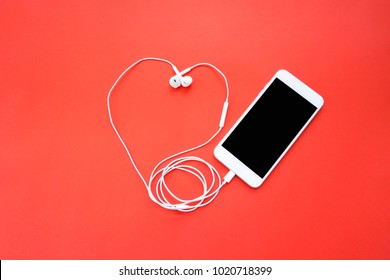 Smartphone and Earphones in Heart Shape on Red Background Top View