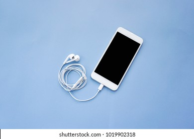 Smartphone with Earphones on Blue Background Top View
