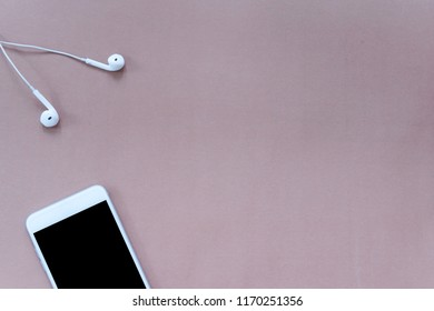 Smartphone and Earphones on Brown Background Top View