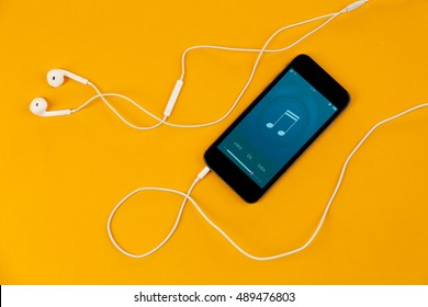 Smartphone with earphones on color background