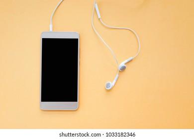 Smartphone and Earphones on Orange Background Top View