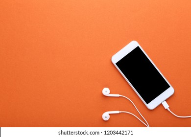 Smartphone with earphones on orange background