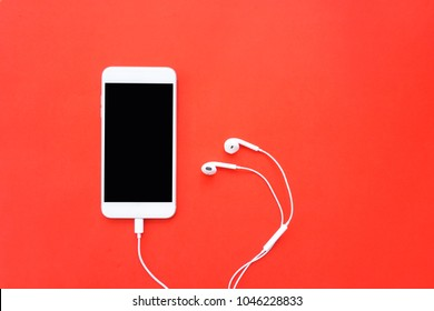Smartphone with Earphones on Red Background Top View