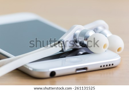 Smartphone and earphones on table.  Focus on earphones.