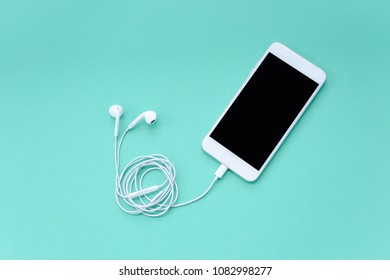 Smartphone with Earphones on Turquoise Background Top View