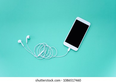 Smartphone and Earphones on Turquoise Background Top View