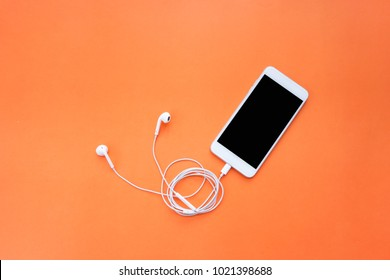 Smartphone and Earphones with Spiral Cable on Orange Background Top View